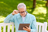 senior man with tablet pc at summer park
