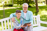 grandfather and boy with tablet pc at summer park