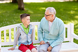 grandfather and grandson talking at summer park