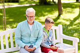 old man and boy with smartphones at summer park