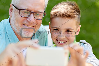 old man and boy taking selfie by smartphone