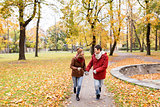 happy young couple running in autumn park