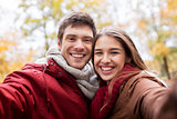 happy young couple taking selfie in autumn park