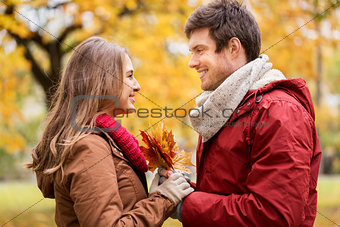 happy couple with maple leaves in autumn park