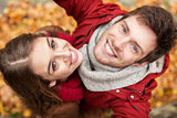 close up of happy couple taking selfie at autumn