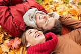 close up of smiling couple lying on autumn leaves