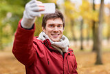 man taking selfie by smartphone in autumn park