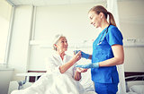 nurse giving medicine to senior woman at hospital