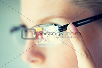 close up of woman in glasses with virtual screen