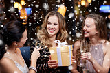 happy women with champagne and gift at night club