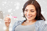 happy woman looking at home pregnancy test