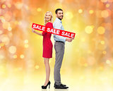 couple with red sale sign standing to back