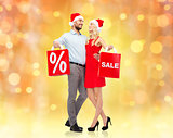 happy couple in santa hats with red shopping bags