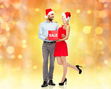 happy couple in santa hats with red sale sign