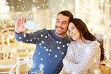 couple taking smartphone selfie at cafe restaurant
