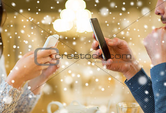 close up of couple with smartphones at cafe