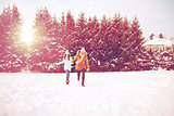 happy couple running in winter snow