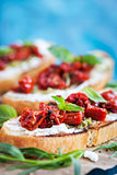Bruschetta with cream cheese, pesto, fresh basil and sun dried t