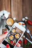 Taking food photo of breakfast with fried eggs by smart phone
