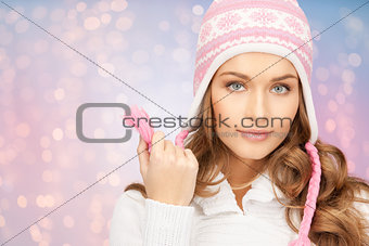 close up of woman in hat and scarf over lights