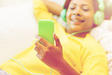 happy african woman with smartphone and headphones