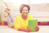 happy african woman with tablet pc and headphones