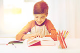 smiling, student boy reading book at home