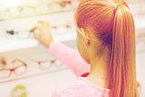 close up of girl choosing glasses at optics store