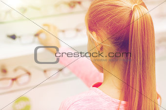 close up of girl choosing glasses at optics store