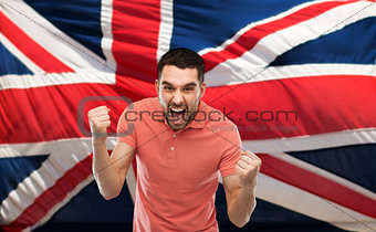 angry man showing fists over british flag
