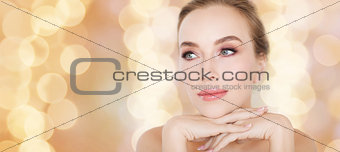 beautiful young woman face and hands over lights