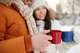 close up of happy couple with tea cups in winter