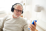 happy senior man with smartphone and headphones