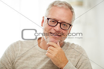 close up of smiling senior man in glasses thinking