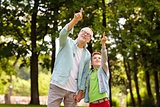 grandfather and boy pointing up at summer park