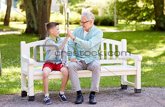 old man and boy making high five at summer park