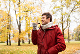 man recording voice on smartphone at autumn park