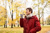 man recording voice on smartphone at autumn park
