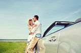 happy couple hugging near cabriolet car at sea