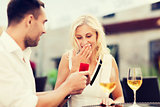 happy couple with engagement ring and wine at cafe