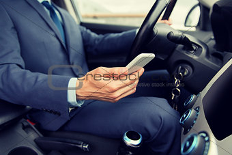 close up of man with smartphone driving car