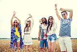 happy young hippie friends dancing outdoors