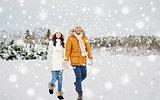 happy couple walking along snowy winter field
