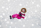 happy little kid or girl in winter clothes on snow