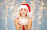 happy woman in santa hat holding fairy dust