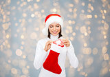woman in santa hat with gift box and stocking