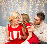 happy family with christmas gift kissing