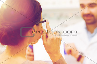 close up of woman choosing glasses at optics store