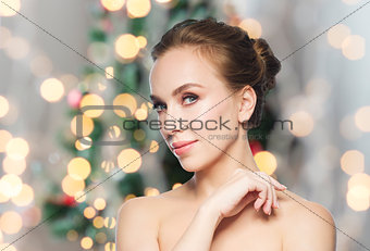 beautiful young woman face over christmas lights