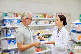 pharmacist and senior man buying drug at pharmacy